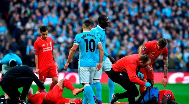 Liverpool's French defender Mamadou Sakho and Liverpool's German midfielder Emre Can are treated after a clash of heads