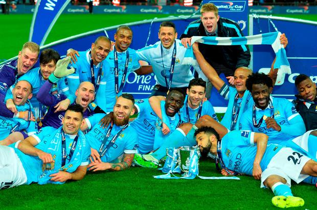 Manchester CIty players pose with the League Cup during the presentation after Manchester City won the penalty shoot-out