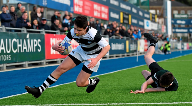 Belvedere College's Cian Rogers goes over to score a try despite the tackle of Daniel O'Connor from Newbridge College. Photo: Stephen McCarthy/Sportsfile