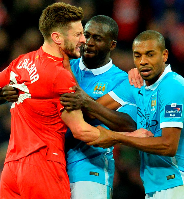 Liverpool's Adam Lallana fights with Manchester City's Fernandinho (r) and Yaya Toure. Photo: Glyn Kirk/AFP/Getty Images