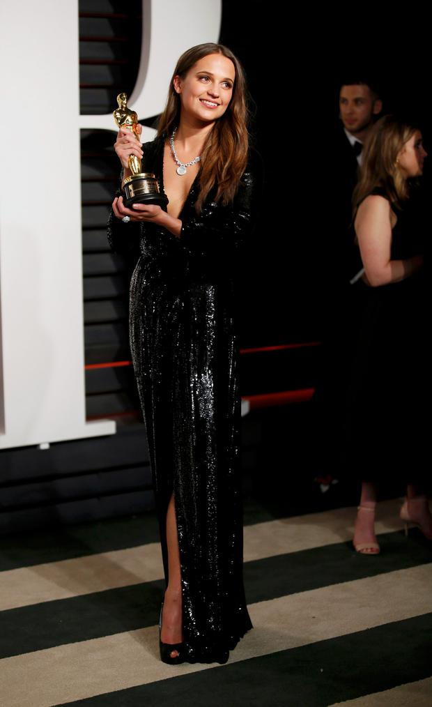 Alicia Vikander holding her Oscar for Best Supporting Actress for her role in the film