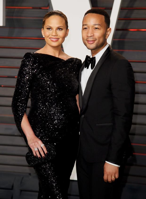 Model Chrissy Teigen and her husband musician John Legend (R) arrive at the Vanity Fair Oscar Party in Beverly Hills, California February 28, 2016. REUTERS/Danny Moloshok