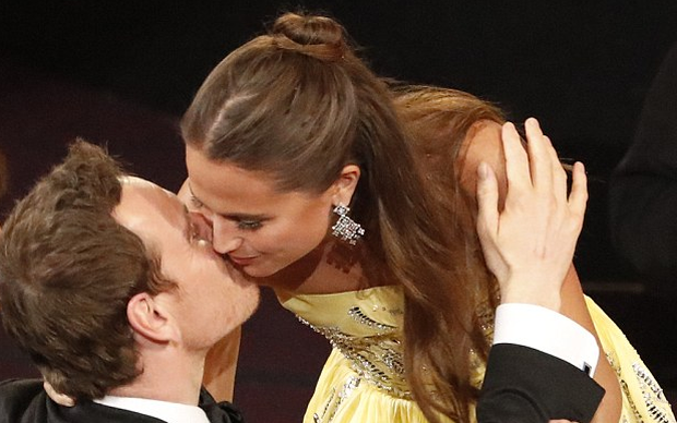 Alicia Vikander plants a kiss on Michael Fassbender's cheek as she is announced Best Supporting Actress at the Oscars. Photo: ABC
