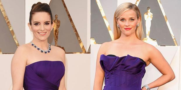 Tina Fey and Reese Witherspoon chose similar purple gowns for the Oscars. (Photo: Getty).