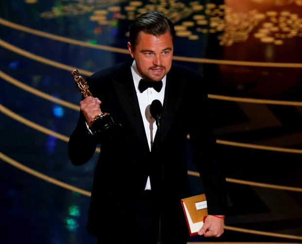 Leonardo DiCaprio holds the Oscar for Best Actor for the movie