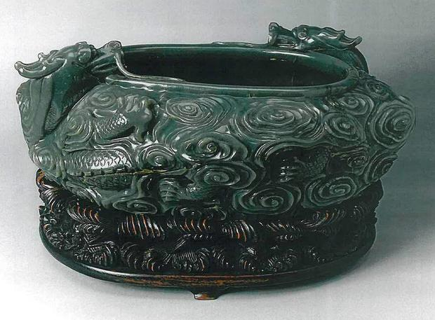 18th century Chinese jade bowl with a Chinese poem inscribed on it, on its wood carved stand, one of two items stolen from Durham University's Oriental Museum Credit: Durham Police/PA Wire