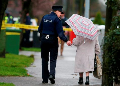 A garda escorts an elderly lady past the crime scene.