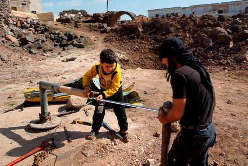 Civilians fix damaged water pipes in the rebel held al-Ghariyah al-Gharbiyah town, in Deraa province, Syria. Photo: Reuters