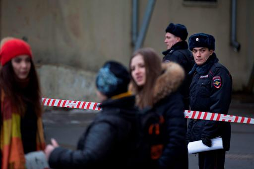 Russian police officers, right and below, secure the area after arresting a woman who was waving the severed head of a small child outside a Moscow subway station