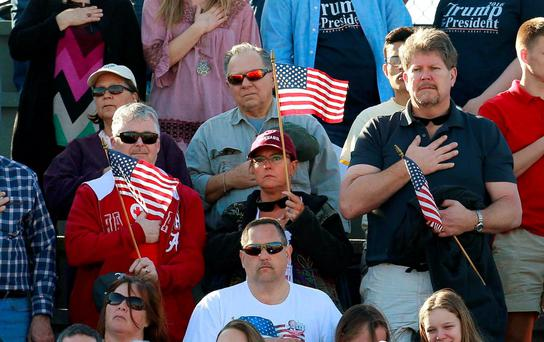 Supporters of US Republican presidential candidate Donald Trump fly US flags during the national anthem at a rally at Madison City Schools Stadium in Madison, Alabama. Photo: Reuters