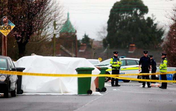 A police forensic officer stands near to a shattered car window at the scene of a shooting on McKee Road in Finglas