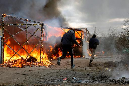 Migrants run past burning tents in a makeshift camp near Calais, France, Monday Feb. 29, 2016. French authorities have begun dismantling part of the sprawling camp locally referred to as