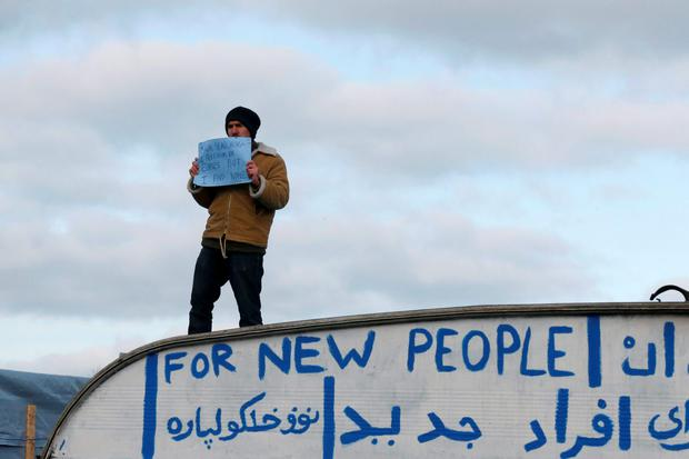 A migrant stands on the roof of a shelter and displays the message,