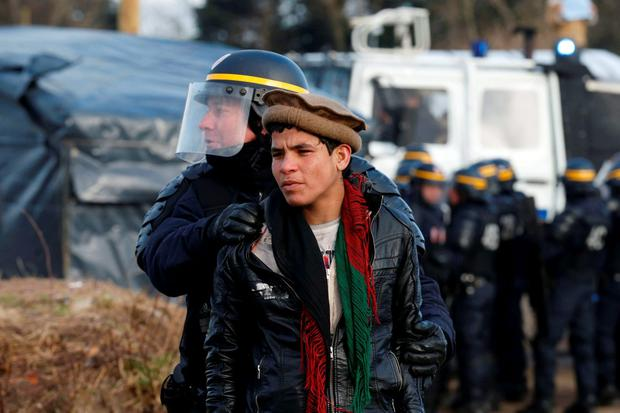A French CRS riot policeman apprehends a young Afghan during a protest by migrants against the partial dismantlement of the camp for migrants called the