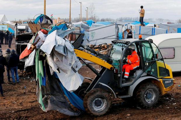A bulldozer clears away debris from makeshift shelters that are torn down in a section of the camp for migrants called the