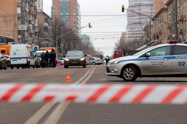 Police and the Investigative Committee cars secure an area abound a subway station in Moscow on Monday, Feb. 29, 2016. Russian news agencies report that police have arrested a woman who was waving the severed head of a small child outside a Moscow subway station