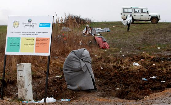 A refugee from Afghanistan waiting for a permission to cross the border at Macedonia Credit: Boris Grdanoski