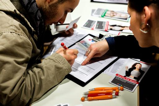 A refugees fills a form at a stand offering employment and job training possibilities at a jobs fair for refugees in Berlin Credit: Carsten Koall (Getty Images)