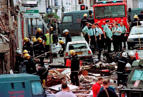Police and firefighters inspecting the damage caused by a bomb in Omagh, Co Tyrone, in 1998. Photo: PA Wire