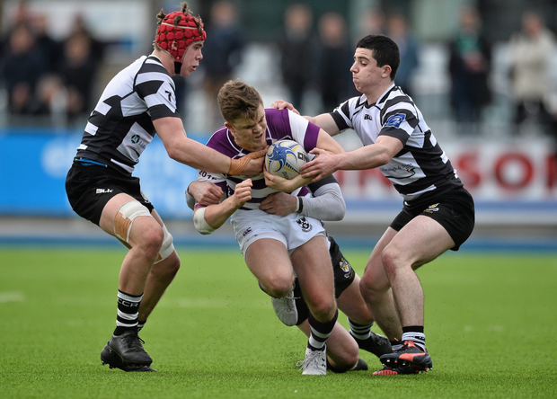 Michael Silvester, Clongowes Wood College, is tackled by Jack Canning, left, and Philip O'Shea, Cistercian College Roscrea (SPORTSFILE)