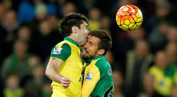 Robbie Brady collides with his Norwich team-mate Gary O'Neill during last night's game against Chelsea: Reuters / John Sibley