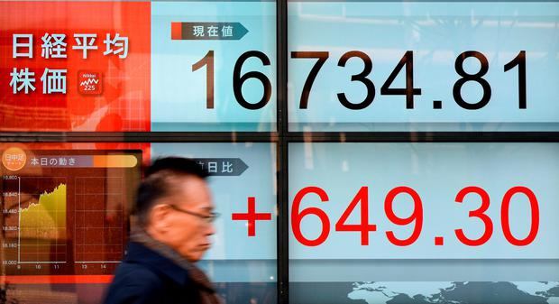 A businessman walks past an electric quotation board flashing the Nikkei key index of the Tokyo Stock Exchange (TSE). Photo: Getty Images