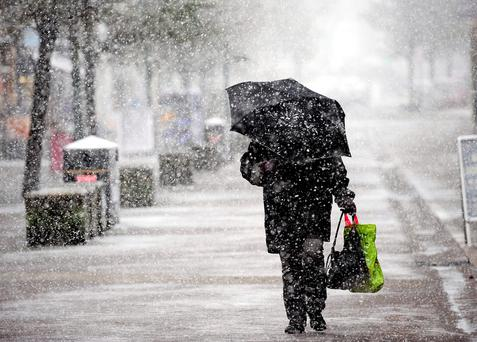 A person shelters under an umbrella in Buxton town centre, Derbyshire, as forecasters said that Storm Jake may bring ice, snow and 70mph winds. Photo: John Giles/PA Wire