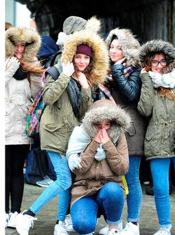 Italian students visiting Athlone huddle against heavy rain and strong winds. Photo: James Flynn