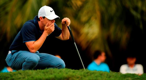 Rory McIlroy lines up a putt on the 11th hole