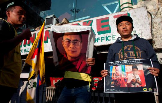 An exile Tibetan carries a portrait of his spiritual leader the Dalai Lama while another holds a poster with portraits of two Tibetans, who exiles claim have immolated themselves demanding freedom for Tibet, during a candlelit vigil in Dharmsala, India. (AP Photo/Ashwini Bhatia)