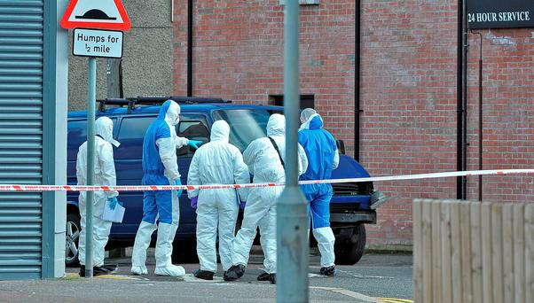 Police forensic experts examine the scene of an under-car bomb that exploded under a van and injured a prison officer in Belfast. Photo: Photopress