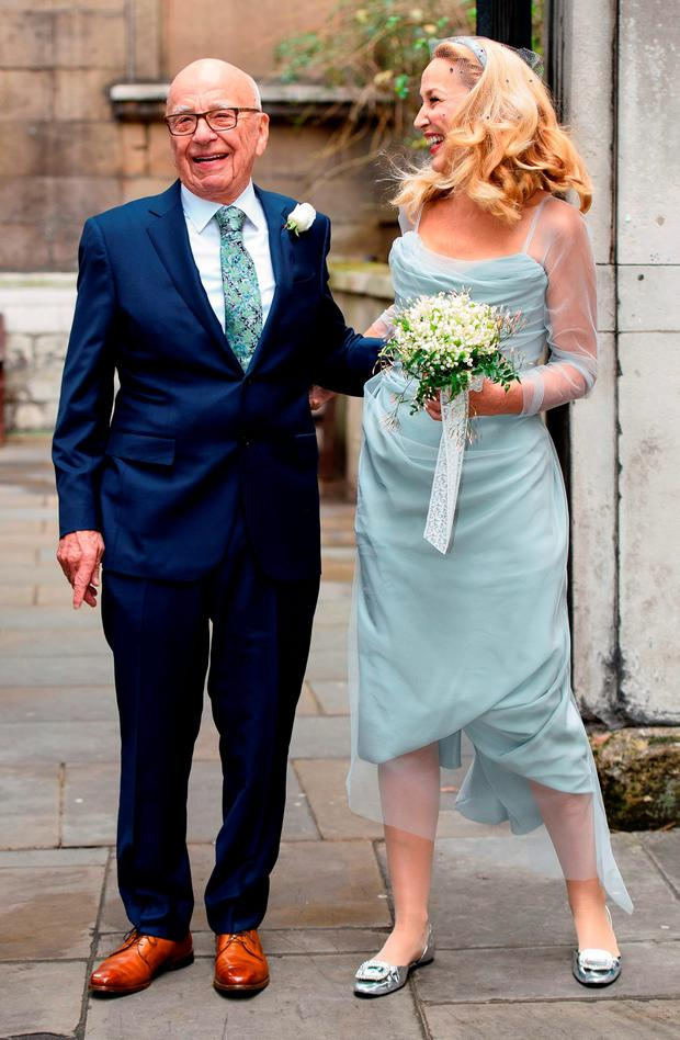 Australian born media magnate Rupert Murdoch (L) and his new bride, former US model Jerry Hall pose for a photograph outside St Bride's church on Fleet Street in central London on March 5, 2016, after attending a ceremony of celebration of their marriage