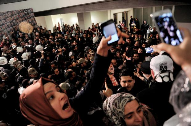 Journalists react as riot police enter the headquarters of Zaman. The police raid came hours after a court placed it under the management of trustees Credit: AP
