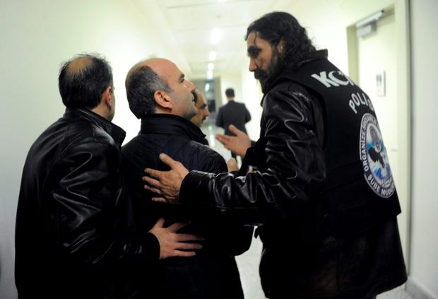 Abdulhamit Bilici (C), editor-in-chief of Zaman, as police escort him from the building. The move against the paper, which is linked to an opposition cleric, heightened concerns over deteriorating press freedoms in the country Credit: AP