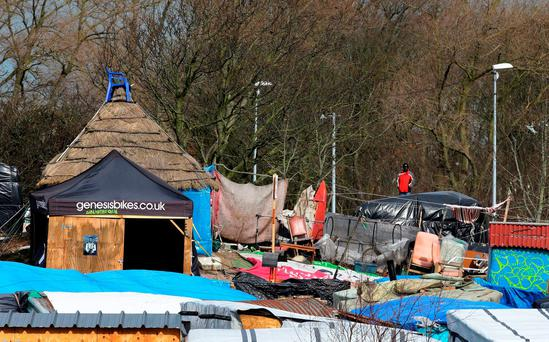A man looks over the Calais migrant camp known as the Jungle as a third successive day of clearing the slum of makeshift homes resumed. Photo: Gareth Fuller/PA Wire