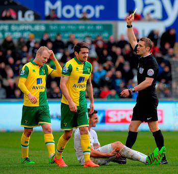 Robbie Brady (2nd L) of Norwich City is shown a yellow card by referee Craig Pawson (1st R) during the Barclays Premier League match between Swansea City and Norwich City at Liberty Stadium