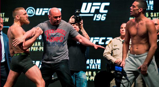 Conor McGregor, left, is held back by Dana White while charging opponent Nate Diaz