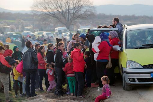Migrants crowd next to a car to receive clothing donations at the northern Greek border station of Idomeni, Saturday, March 5, 2016. (AP Photo/Vadim Ghirda)