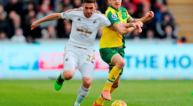 Swansea City's Angel Rangel (left) is challenged by Norwich City's Robbie Brady during the Barclays Premier League match at the Liberty Stadium. Photo: David Davies/PA