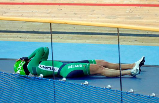 Caroline Ryan of Ireland lies on the track after crashing in the women's points race. REUTERS/Andrew Winning