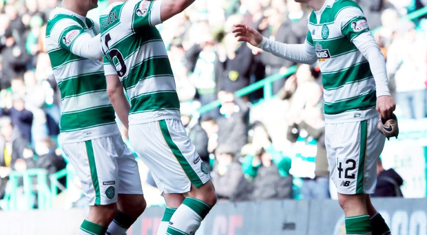 Celtic's Callum McGregor's pick up his shoe after is came off as he celebrates scoring his sides third goal with team mates Leigh Griffiths and Gary Mackay-Steven