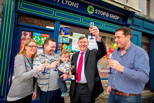Eva Marie, Ahmed, and one-year-old baby Theodore Stewart with Matt and Alan Lyons celebrating outside their family shop in Sligo, where the €8.2 m winning Lotto ticket was sold. Photo: James Connolly