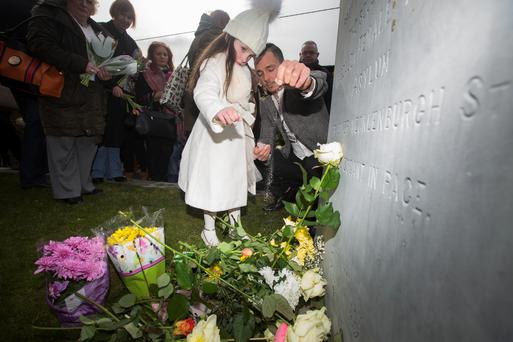 Poppy Bella Tate lays a flower with her father Frankie Tate, who also spread ashes of his grandmother Martina Keogh who was in the Magdalene laundries. Photo: Mark Condren