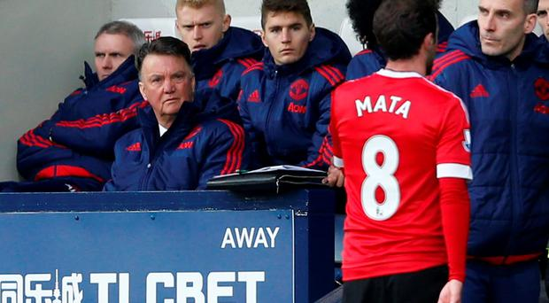 Manchester United's Juan Mata walks down the tunnel after being sent off as manager Louis Van Gaal looks on