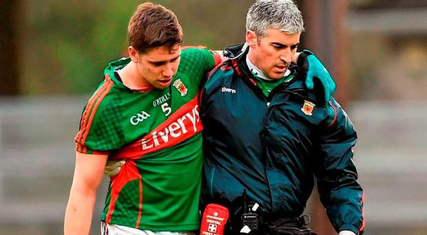 Mayo's Lee Keegan is assisted off the pitch by Dr Sean Moffatt in a suspected case of concussion Credit: Diarmuid Greene (SPORTSFILE)