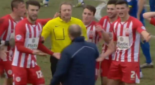 The Accrington players surround the referee to protest as manager John Coleman attempts to calm them TWITTER