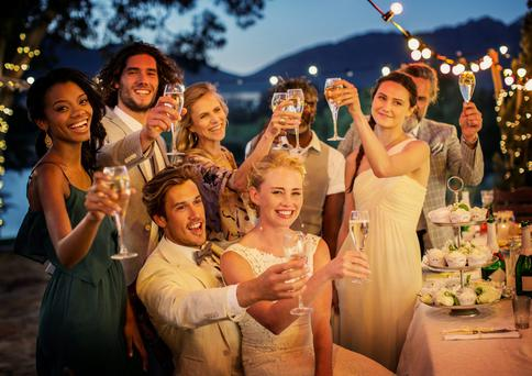 Wedding guests toasting with champagne during wedding reception in garden