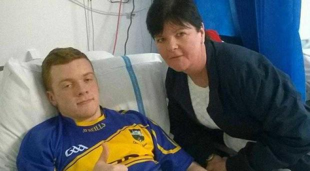 Odhrán McKenna, pictured with teacher Donna Tohill, gives a thumbs up from his hospital bed. Picture credit: Facebook