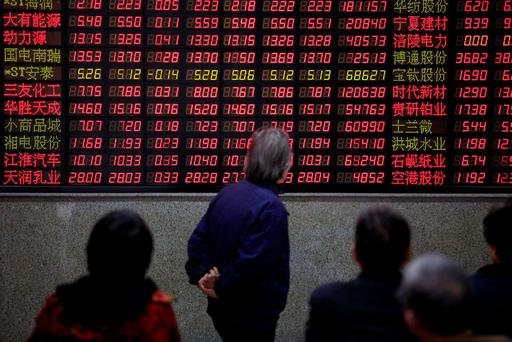 Investors look at an electronic board showing stock information at a brokerage house in Shanghai, China. Photo: Reuters