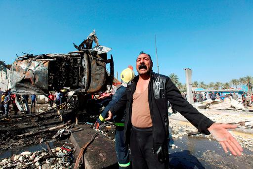 A man reacts at the site of a bomb attack at a checkpoint in the city of Hilla, south of Baghdad. Photo: Reuters